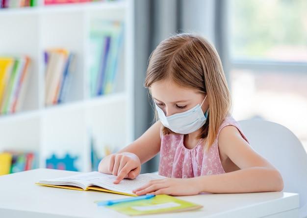 Klein meisje leesboek in de klas tijdens coronavirus pandemie