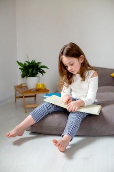 Klein meisje leest en doet huiswerk zittend op het bed concept van onderwijs op afstand onderwijs