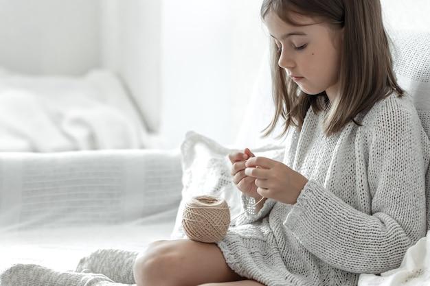 Klein meisje leren breien, thuis vrije tijd en handwerk concept.