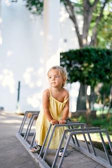 Klein meisje leunt op de reling van de fietsenstalling