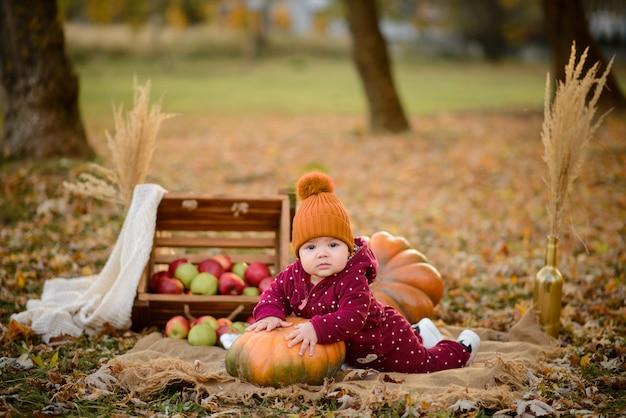 Klein meisje leunt op een pompoen.