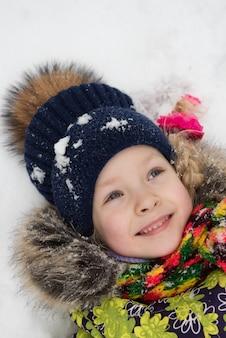 Klein meisje liggend in de sneeuw en lachen om de winterdag.