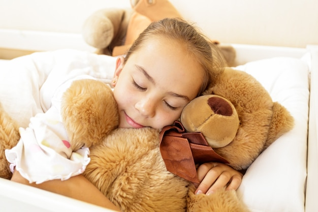 Klein meisje liggend op bed met grote bruine teddybeer