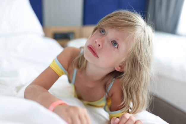 Klein meisje ligt in bed in de kliniek en huilt