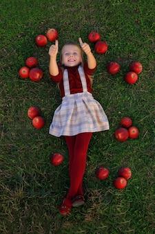 Klein meisje ligt op de grond, omringd door rode appels