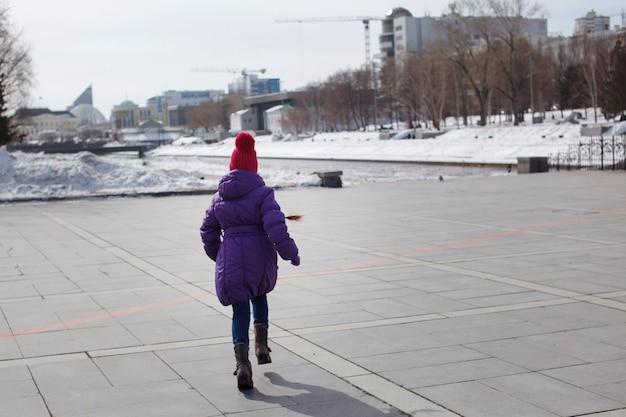 Klein meisje loopt langs de straat, op een geplaveide weg in een moderne stad