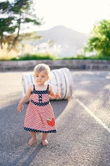 Klein meisje loopt op de parkeerplaats tegen de achtergrond van witte banden