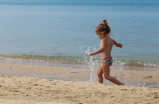 Klein meisje loopt op het strand, vreugdevolle emoties
