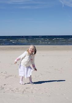 Klein meisje loopt op het strand