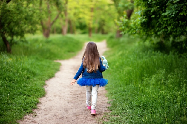 Klein meisje loopt van achteren door het steegje