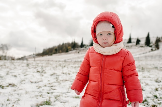 Klein meisje lopen terug op besneeuwde berg, spelen op winteraard.