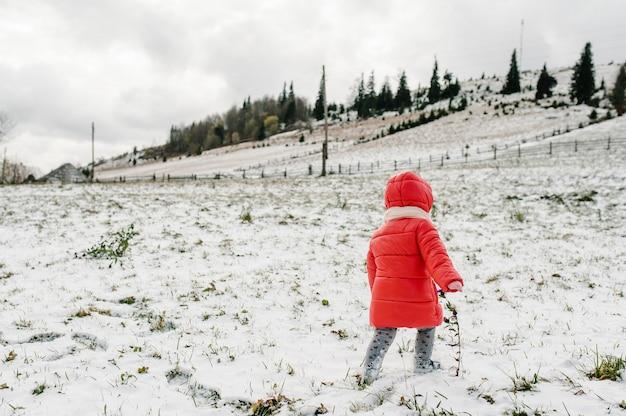 Klein meisje lopen terug op besneeuwde berg, winter natuur. kinderen, dochter die van reis genieten. frost winterseizoen. concept gelukkig gezin.