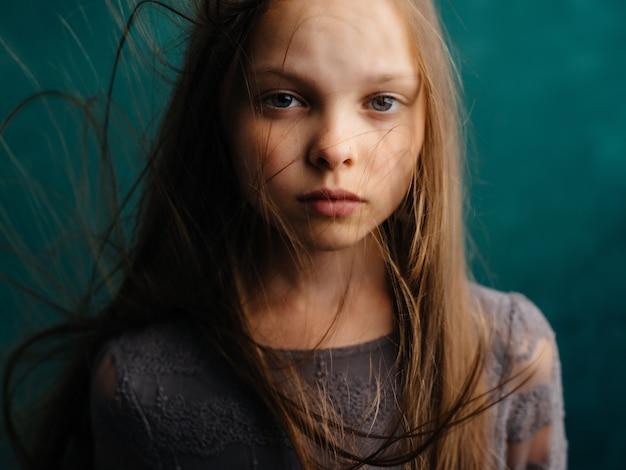 Klein meisje los haar close-up groene achtergrond emoties depressie. hoge kwaliteit foto