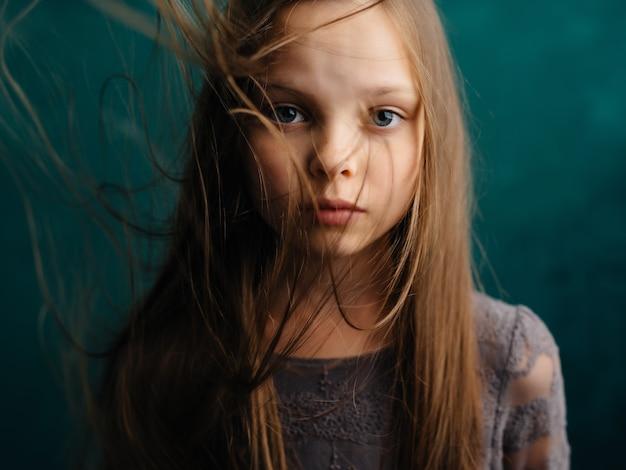 Klein meisje los haar close-up groene achtergrond emoties depressie
