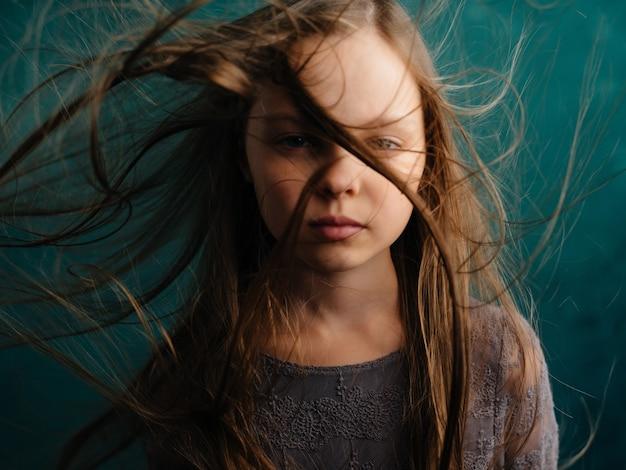 Klein meisje los haar groene achtergrond ontevredenheid emoties