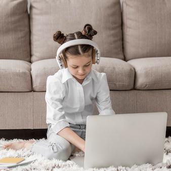 Klein meisje luistert naar haar leraar via een koptelefoon op de vloer