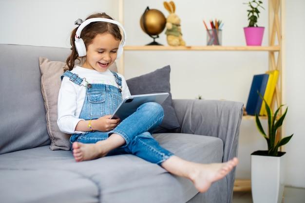 Klein meisje luistert naar muziek via een koptelefoon
