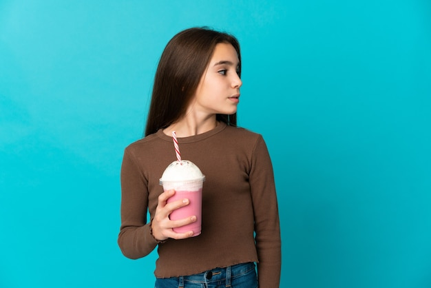 Klein meisje met aardbeienmilkshake geïsoleerd op een blauwe achtergrond op zoek naar de zijkant