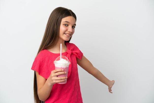 Klein meisje met aardbeienmilkshake over geïsoleerde witte achtergrond die de handen naar de zijkant uitstrekt om uit te nodigen om te komen