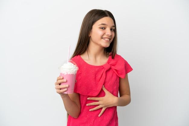 Klein meisje met aardbeienmilkshake over geïsoleerde witte achtergrond die veel glimlacht