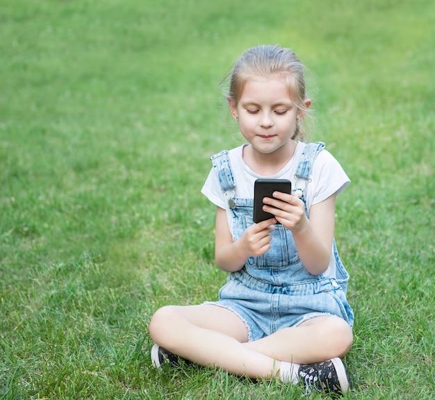 Klein meisje met behulp van een smartphone in het park