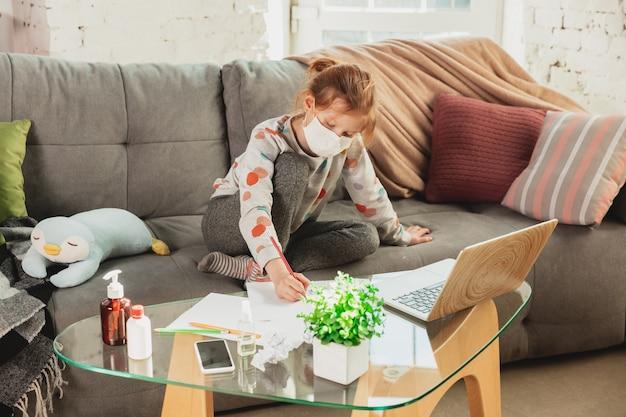Klein meisje met beschermend masker thuis geïsoleerd met coronavirus luchtwegsymptomen zoals koorts, hoofdpijn, hoest in milde toestand. gezondheidszorg, medicijnen, quarantaine, behandelingsconcept. voelt ziek.