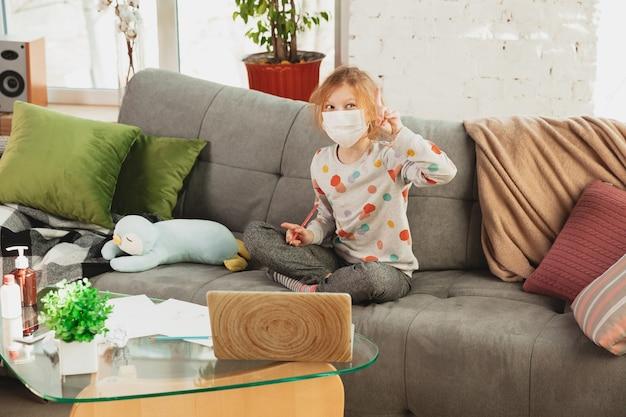 Klein meisje met beschermend masker thuis geïsoleerd met coronavirus