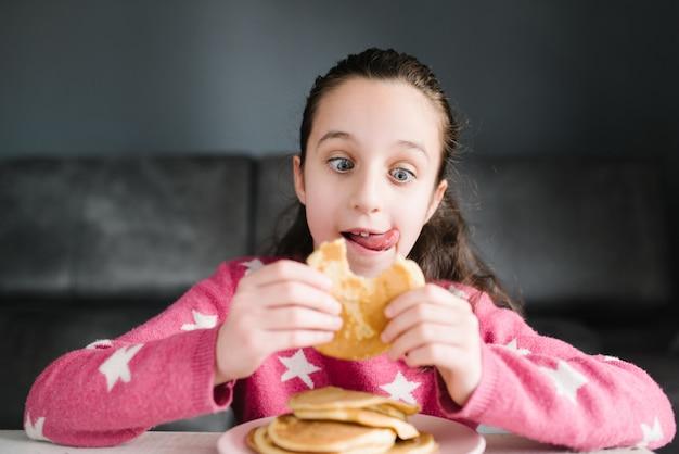 Klein meisje met blauwe ogen, het dragen van een roze trui. ze zit op de bank pannenkoeken te eten. het kleine meisje steekt haar tong uit van smaak en wil ze eten.