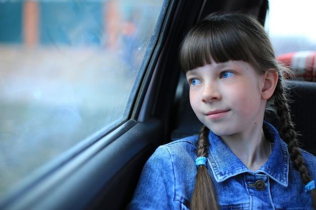 Klein meisje met blauwe ogen zitten in de achterkant van de auto bij het raam