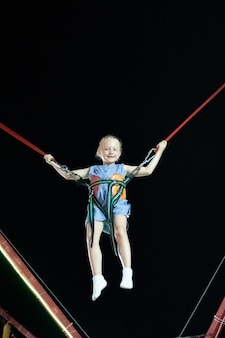 Klein meisje met blond haar in de lucht op de katapultrit tegen de zwarte lucht. leuke zomervakantie.