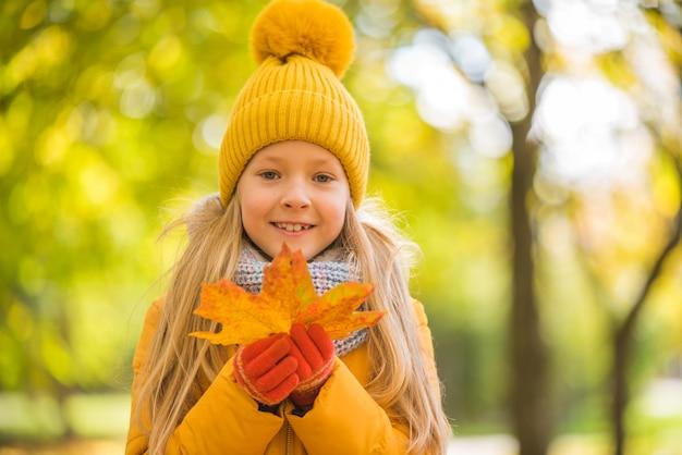 Klein meisje met blond haar op herfstachtergrond in gele kleding