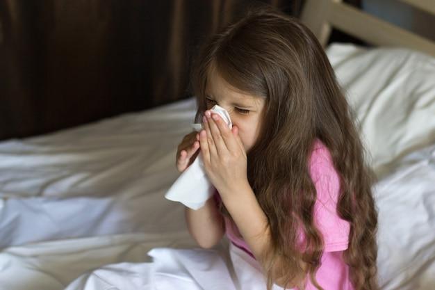 Klein meisje met blond haar zit op het bed te niezen en gebruikt een handdoek om het snot van haar neus te vegen
