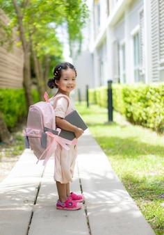 Klein meisje met boek en rugzak wandelen in het park klaar terug naar school
