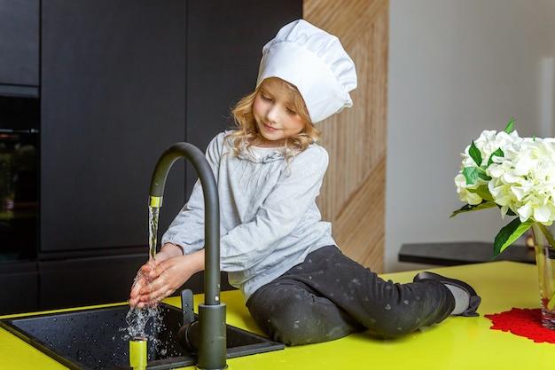 Klein meisje met chef-kok hoed leren koken glimlachend in de keuken. kind dat thuis gezond voedsel bereidt en plezier heeft. jeugd, eten, gezond eten, huishouden, teamwork, helpen, familieconcept