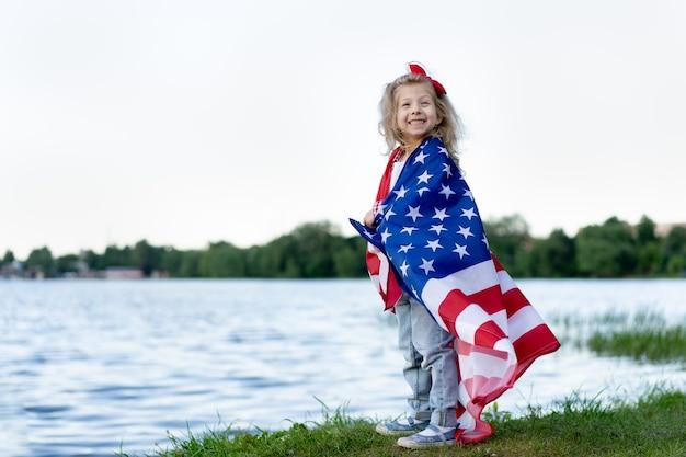 Klein meisje met de amerikaanse vlag in de natuur, het concept van patriottisme en de vakantie van onafhankelijkheid vs. veteranendag vs.
