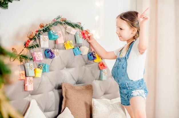 Klein meisje met de huidige doos handgemaakte adventskalender thuis. diy kerst adventskalender voor kinderen