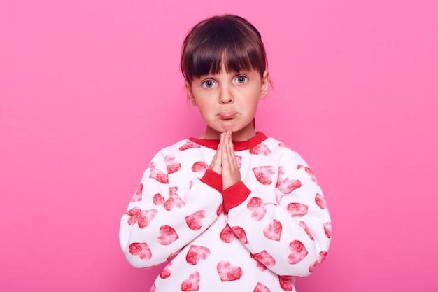 Klein meisje met donker haar kijkt naar de camera met een smekende uitdrukking op haar gezicht, houdt de handpalmen bij elkaar, bidt, draagt een trui, geïsoleerd over roze muur.