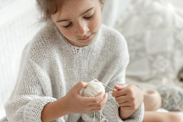 Klein meisje met draden leert haken, vrije tijd thuis en handwerken.