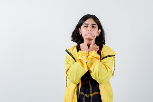 Klein meisje met droevig gebaar met vingers op gezicht in geruit overhemd, jasje en schattig, vooraanzicht.