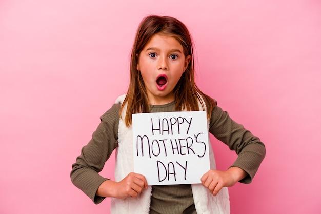 Klein meisje met een banner voor gelukkige moeders dag geïsoleerd op roze achtergrond