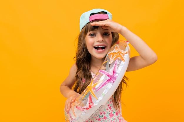 Klein meisje met een baseballcap in een zwembroek met een cirkel zwemmen op een oranje muur