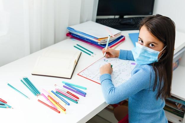 Klein meisje met een beschermend masker op afstand thuisonderwijs, quarantaine