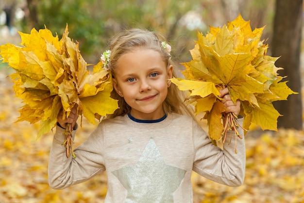 Klein meisje met een boeket herfstbladeren. meisje in park tegen de gevallen bladeren met twee boeketten van gouden esdoornbladeren.