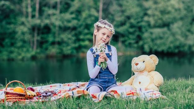 Klein meisje met een boeket madeliefjes zittend op het gazon op een zomerdag.