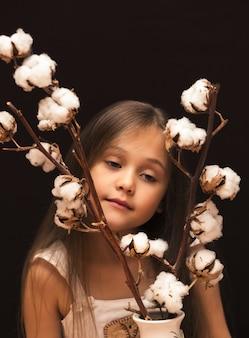 Klein meisje met een boeket van katoen