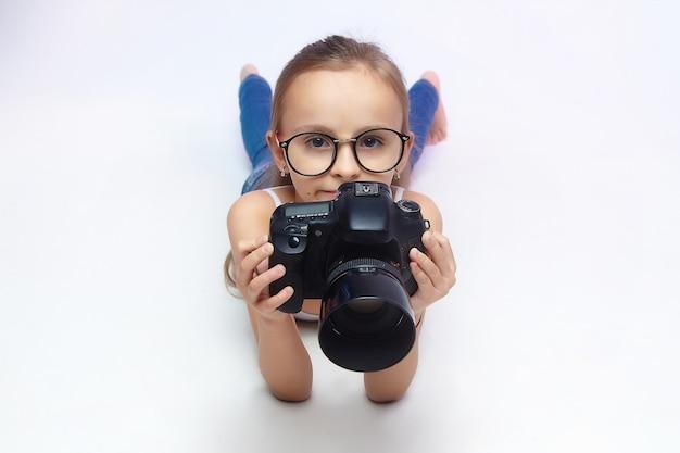 Klein meisje met een bril, liggend in de studio met een camera.
