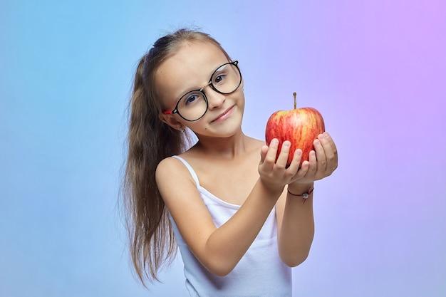 Klein meisje met een bril, met een rode appel.