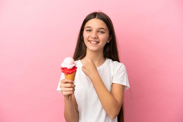 Klein meisje met een cornetroomijs over geïsoleerde roze achtergrond die een overwinning viert