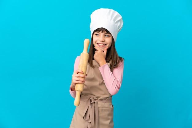Klein meisje met een deegroller geïsoleerd op een blauwe achtergrond, kijkend naar de zijkant en glimlachen