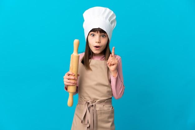 Klein meisje met een deegroller geïsoleerd op een blauwe achtergrond met de bedoeling de oplossing te realiseren terwijl ze een vinger optilt